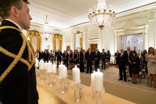 """President Donald J. Trump and First Lady Melania Trump join guests in singing """"America the Beautiful"""" during a reception in honor of Gold Star Families Sunday, Sept. 27, 2020, in the East Room of the White House."""