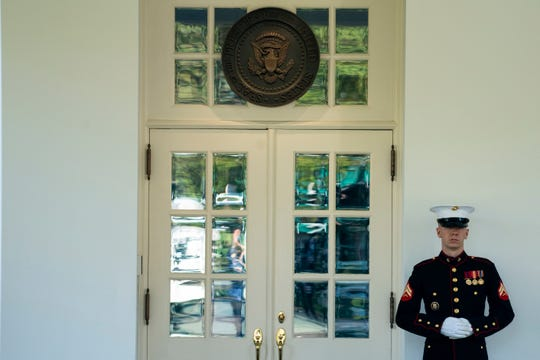 A Marine is posted outside the West Wing of the White House, signifying the president is in the Oval Office on Wednesday.