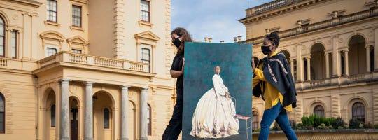 Artist Hannah Uzor, right, and Kirsty Huggett carry Uzor's painting.
