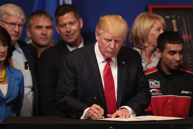 President Donald Trump signs an executive order to try to bring jobs back to American workers and revamp the H-1B visa guest worker program during a visit to the headquarters of tool manufacturer Snap-On on April 18, 2017, in Kenosha, Wis.