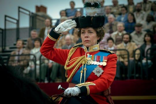 "Olivia Colman raises a salute as Queen Elizabeth II in ""The Crown."""