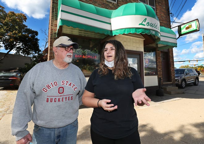 """Dave """"Louie"""" Khoury, owner of Louie's Bar & Grille, listens to his granddaughter, manager Gia Ingarra, tell how her parents met at the Akron restaurant and how she met her fiance there too."""