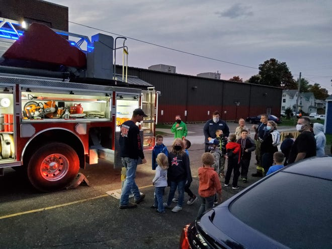 Lexington Township Volunteer Fire Department staff show off various parts of a fire vehicle during a visit with an area Cub Scout troop.