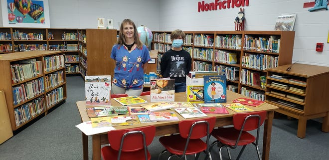 Oak Hall student Willa Harvey delivers a collection of books focusing on diverse characters and themes to Plainview Elementary School librarian Stacy Wilson. Harvey spent the summer compiling the books and delivered several similar collections to local elementary schools on Thursday.