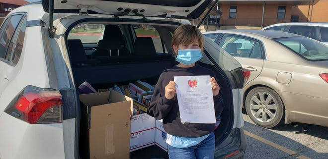 Willa Harvey with a carload full of books to be delivered to local elementary school libraries. Each box contains books for a different school, and she is holding a letter she composed that she presents along with the books.