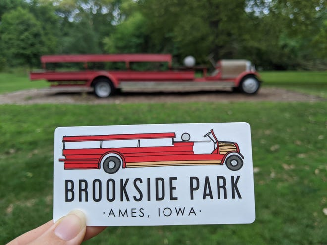 Artist Naomi Friend hold the Brookside Park sticker she created with the park's iconic firetruck in the background.