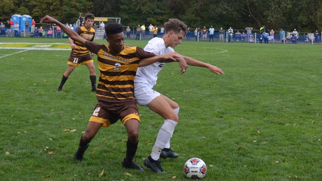Delran defender CJ Rogers (2) battles Nic Torres of Holy Cross for the ball during Wednesday's Burlington County Scholastic League game.