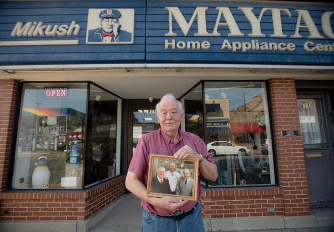 """Robert """"Bob"""" Mikush stands in front of the family's business on Merchant Street in Ambridge holding a photo of his late father, Andrew Mikush Jr., his late brother, Andrew """"Whitey"""" Mikush III, and himself."""