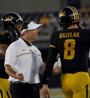 Missouri head football coach Eli Drinkwitz talks with quarterback Connor Bazelak (8) during a Southeastern Conference game against Alabama on Sept. 26 at Faurot Field.