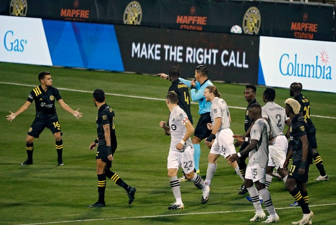 Referee Victor Rivas calls for a penalty kick after a video review confirmed Columbus Crew SC midfielder Hector Jimenez (16), left, fouling Montreal Impact forward Bojan Krkic (9) in the box during the 2nd half of their MLS game at MAPFRE Stadium in Columbus, Ohio on October 7, 2020.