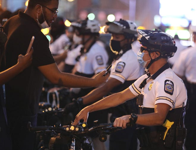 Black Lives Matter protesters photograph Columbus police officers after being pushed back to the sidewalk on July 31. Protesters had blocked the northbound lanes of South High Street in front of the Statehouse. [Fred Squillante/Dispatch]