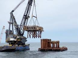 Crews work to topple Exxon's decommissioned Lena platform in July about 50 miles southeast of Grand Isle, where it will serve as an artificial reef to attract fish and the anglers who catch them.
