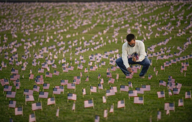 Volunteers place 200,000 American flags to memorialize deaths due to COVID-19 on the National Mall on Sept. 21.