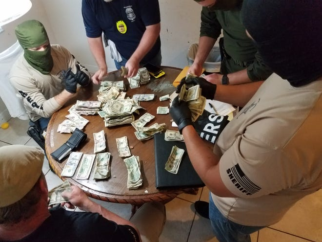 Flagler County Sheriff's Office deputies and task force members count money seized during a search of a drug house.