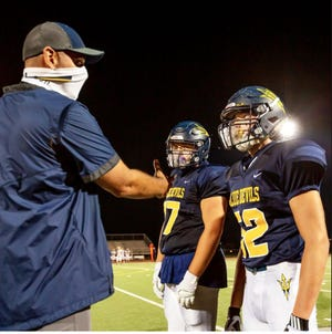 Greencastle-Antrim assistant football coach Mike Hull, left, spoke with Jake Kumfert, center, and John Redos during the Oct. 2 game against Waynesboro. The coach wore a gaiter, while the players had protective shields in their helmets.