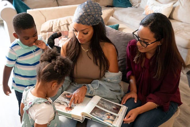 From left, siblings Zavion, Jazzmyn, Katherine and Jennifer Guzman of Newark, N.J., look at pictures of Zavion as an infant. Their mother, Lunisol Guzman, who as a single mother raised three children and adopted two more in her late 40s, died of COVID-19, leaving 4-year-old Zavion and 2-year-old Jazzmyn motherless. Guzman's adult daughters, Katherine Guzman, 32, and  Jennifer Guzman, 28, have stepped up to raise the children.