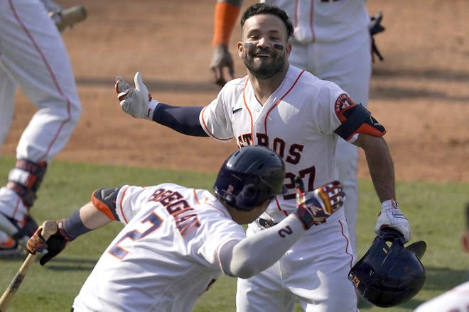 The Houston Astros' Jose Altuve (top) is congratulated by Alex Bregman after hitting a two-run home run against the Oakland Athletics Thursday during the seventh inning of Game 4 of an American League Division Series in Los Angeles. [ASHLEY LANDIS / AP]