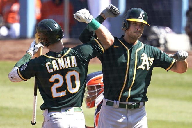 Oakland Athletic Matt Olson (right) is congratulated by Mark Canha after hitting a solo home run against the Houston Astros during Game 3 of an American League Division Series in Los Angeles Wednesday. [MARCIO JOSE SANCHEZ / AP]