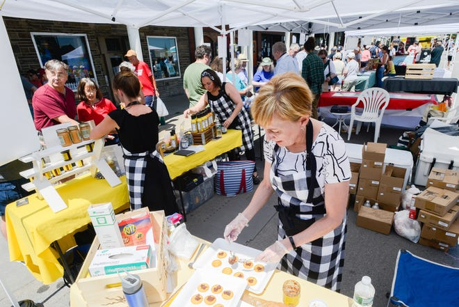 In this 2019 file photo, Farmer Street Pantry employee Suzanne Thayer organizes cracker samples on a tray during the Little Falls Cheese Festival.