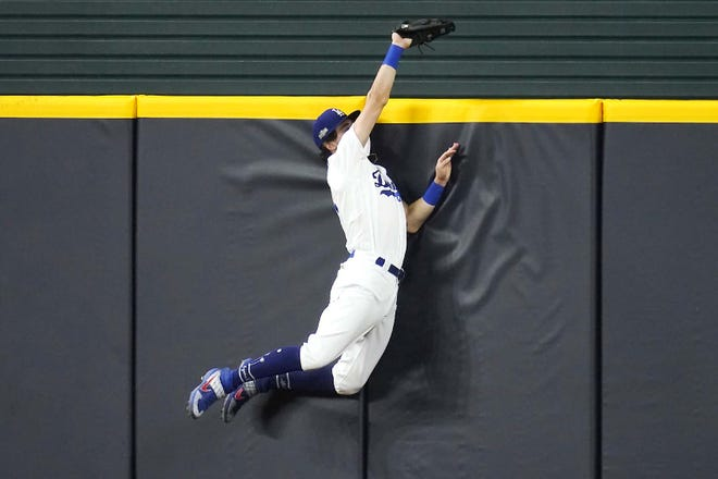 Los Angeles Dodger Cody Bellinger slams into the outfield wall and makes the catch as he robs San Diego Padre Fernando Tatis Jr of a home run during the seventh inning of Game 2 of a National League Division Series Wednesday in Arlington, Texas. [SUE OGROCKI / AP]