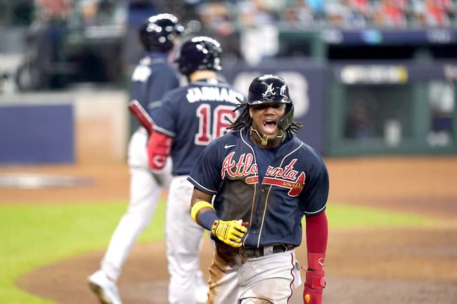 Atlanta Brave Ronald Acuna Jr celebrates after scoring during the third inning of Game 3 of a National League Division Series against the Miami Marlins Thursday in Houston. [ERIC GAY / AP]