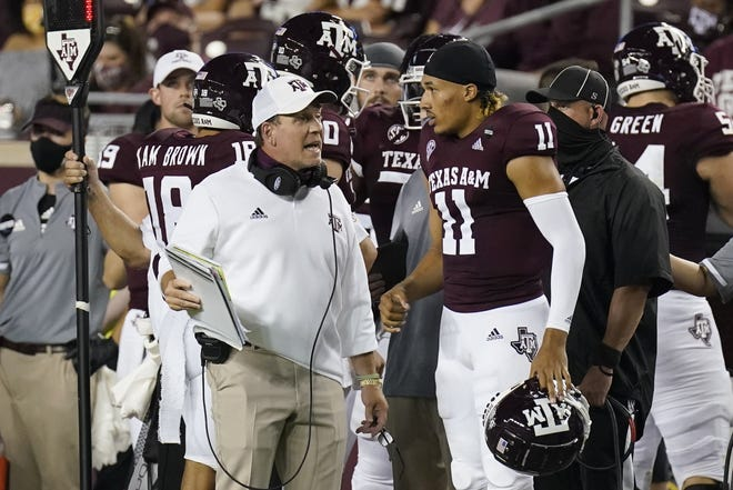 Texas A&M coach Jimbo Fisher, seen here talking with quarterback Kellen Mond (11) against Vanderbilt, could use a win over No. 4-ranked Florida on Saturday to put Aggies' boosters at ease about the $75 million the school invested in him to make the Aggies a perennial national contender. (AP Photo/David J. Phillip)