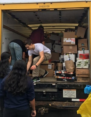 Students from Twinsburg High School load a truck full of food which was sent to The Emergency Assistance Center during the Fill The Bus campaign last year.