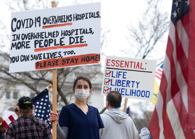 In this April 24, 2020, file photo, a nurse demonstrating in favor of business closures is surrounded by demonstrators against Gov. Tony Evers' restrictions on daily life due to the coronavirus pandemic at the Capitol in Madison, Wis. Doctors and nurses treating those sick and dying from the coronavirus said politics around social distancing and the lethality of the virus are complicating treatment efforts.