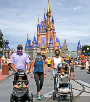 Guests walk on Main Street U.S.A. in front of Cinderella Castle in the Magic Kingdom at Walt Disney World in Orlando on Sept. 30. Walt Disney Co. has announced more layoffs as attendance continues to lag at the major Central Florida theme park due to the COVID-19 pandemic.