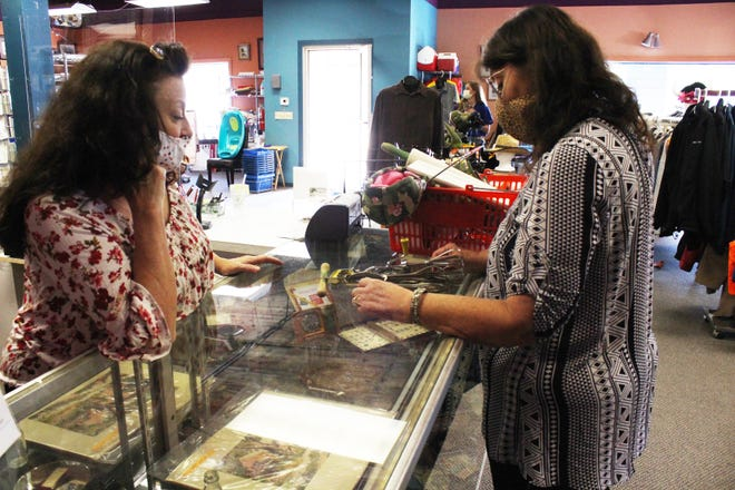 Paws & Shop manager Deena Barnes assists a customer with a sale on the first day open since the COVID-19 pandemic closed the store.