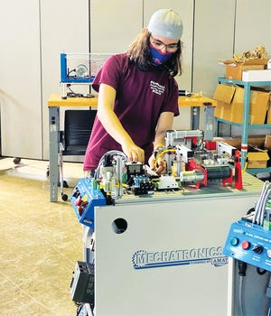 Student Daniel Deuble works on machinery as part of the mechatronics program at the Clinton Higher Education and Workforce Training Facility, which was formerly a National Guard Armory building at the Clinton fairgrounds.