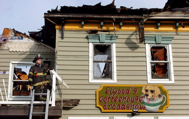 In this December 2007 file photo, then-Utica fire Capt. John Kelly stands on a damaged roof after a fatal fire next door on Columbia Street. Kelly was disciplined in 2018 after a city investigation intoa series of texts between Kelly and Ambrose'sson that referenced lewd acts on fire department property.