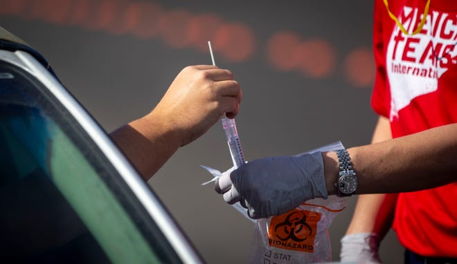Heather Blackburn, a volunteer with Medical Teams Northwest, takes a swab from a person who was accessing COVID-19 testing at the Lane Events Center in Eugene on Oct. 8.