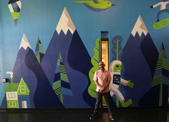 Santiago Uceda in front of his mural at IDX REal Estate Broker, 100 E. Broadway. His distinct, graphic illustrative form brings life and nature to the indoor office.