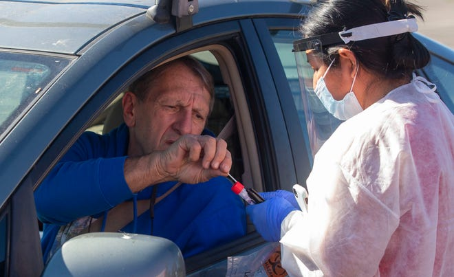 Ronnie Ray Carper takes a swab from Gloria Gonzalez of Lane County Public Health at a drive-thru COVID-19 testing site at the Lane County Fairgrounds on Thursday. The site will be open 2 p.m. to 6 p.m. Friday.