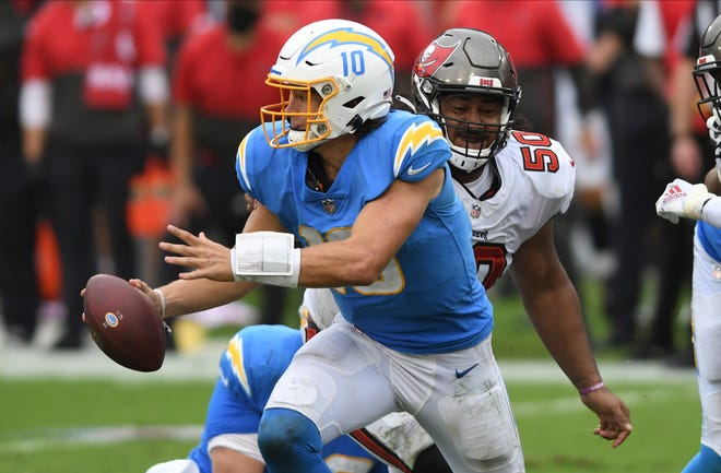 Los Angeles Chargers quarterback Justin Herbert eludes Tampa Bay Buccaneers nose tackle Vita Vea during the second half of Sunday's game in Tampa, Fla.