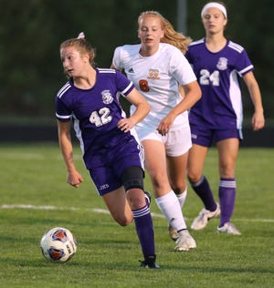 Casey Stalder (42) of Jackson brings the ball upfield while being trailed by Emma Baldinger (6) during their game at Jackson on Wednesday, Oct. 7, 2020. Also visible for the Polar Bears is Kayla Kelley (24).