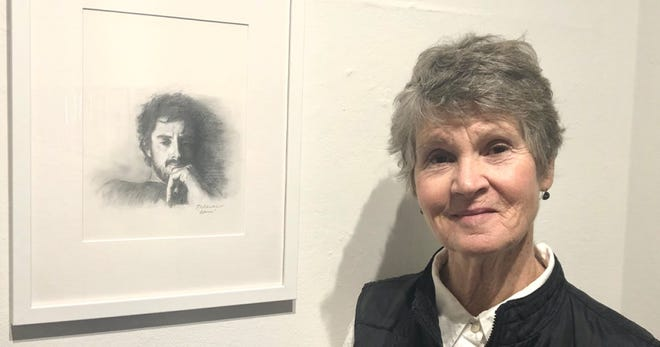 Theresa Clower with the pencil portrait  of her late son that launched the Into Light  project.