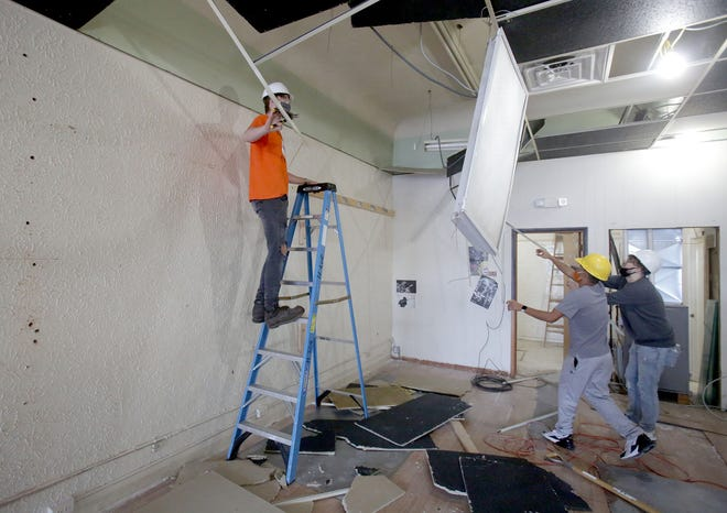Washington High School students Ty Egan (left), Cael Lightfoot and Bryce Paoletto remove a ceiling inside a downtown Massillon building Thursday afternoon as part of a class project. The three seniors are part of the the school's Career Technical Education program. (IndeOnline.com / Kevin Whitlock)