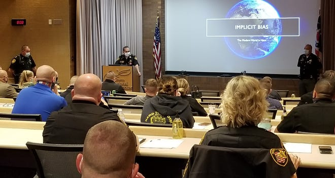 Stark County Sheriff George Maier, behind the podium, talks to a group of Stark County Sheriff's Office staff members. All 253 sheriff's employees are attending training this week, covering topics such as implicit bias, de-escalation and use-of-force techniques.