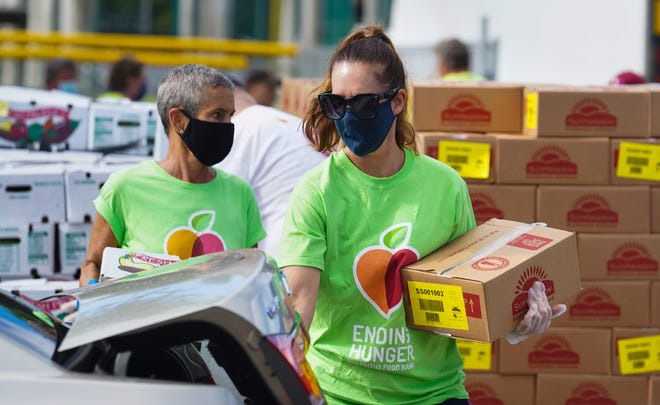 Terri Vitale of All Faiths Food Bank, right, puts a food box into a car during a large-scale food distribution at Sarasota's Ed Smith Stadium in May.
