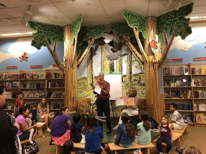 Frank Remkiewicz, the award-winning illustrator of Froggy Series, is assisted by Pine View parent Heidi Bodor at a book reading for Pine View School's Rocket ReadAthon in September 2019 at Barnes and Noble, Sarasota. Pine View Teachers Jenna Molinaro and Mrs Rachel Lenerz listen intently as do some students and parents.