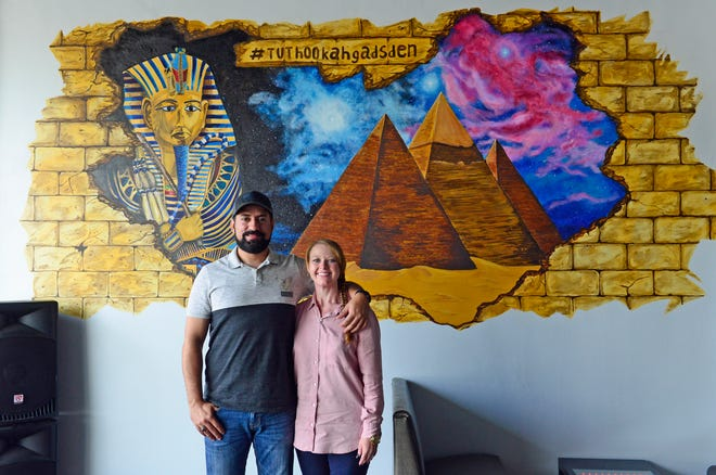 Omar and Rachel Lotfi stand in front of a mural at their business, Tut Hookah Lounge, on Broad Street in Gadsden.