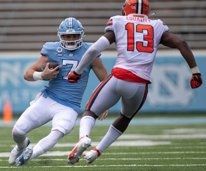 North Carolina quarterback Sam Howell, left, slides in front of Syracuse linebacker Mikel Jones during last month's season opener.