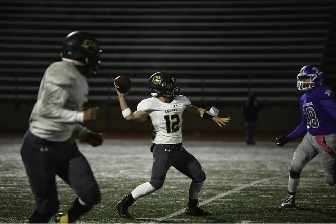 Pueblo County High School quarterback Chase Hartman, middle, launches a pass during a game against Central last season.