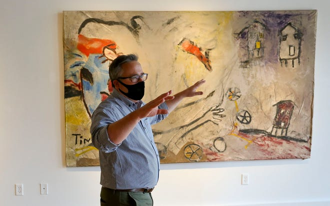 """Museum Director Daniel White discusses paintings done in the 1980s by Charlie Lucas in the Paul Jones Museum downtown, Oct. 8 2020. The exhibition features work by Lucas entitled """"Talking To The Ancestors."""" [Staff Photo/Gary Cosby Jr.]"""