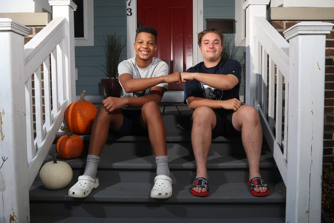 Next-door neighbors Henry Ohlinger (left), 12, and Graham Nelson, 15, have been leading an effort with their families to promote positivity and honor diversity through their cause: Unity in Our Grandview Community. The pair do a fist bump while sitting on the front steps of the Ohlingers' home Oct. 7.