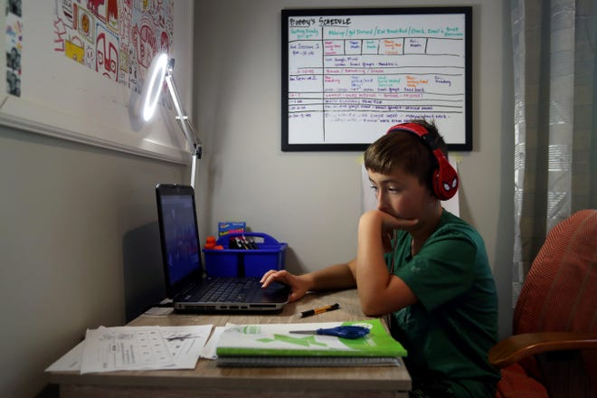 Bobby Barnhart, 9, a third-grader at Griffith Thomas Elementary School, participates in a videoconference with his teacher and fellow Dublin City Schools students in the district's remote-learning academy. He is pictured Oct. 7 at his home in Columbus.