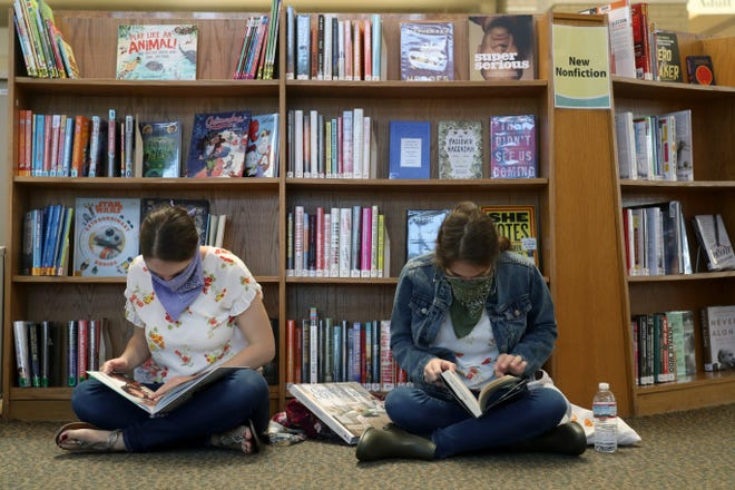 Sisters Mina Gingerich (left) and Lara Gingerich, both of Columbus, browse through a selection of books Oct. 7 at the Upper Arlington Public Library's main branch. The atrium of the main library reopened to the public for limited services Sept. 28.