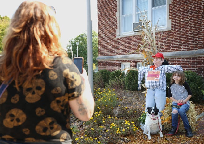 """Sara Walker takes a photo of son Tristan, 11, and their dog, Dora, with """"Scary Larry"""" in front of the Pickerington-Violet Township Historical Society on Oct. 6. """"Scary Larry"""" was part of the Scarecrow Trail."""